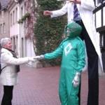 Der Alien (Stelzen-Walk Act) gibt einer Passantin die Hand