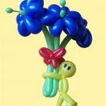 Luftballonblumen sind zu einem Strauß gebunden, von einem Ballonmännchen gehalten.