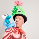 Ballonkünstler Felix beäugt skeptisch eine Luftballon-Schlange auf seiner Schulter